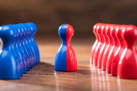 Two Rows Of Pawns Coming Together And Merging On Wooden Table