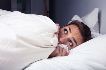 Scared Woman Pulling Bed Sheet Over Self On Bed At Night