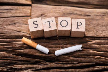 Primo piano di una sigaretta e di blocchi di legno che mostrano la parola di arresto sullo scrittorio