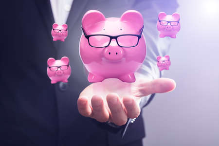 Close-up Of A Pink Piggy Banks Floating In Mid-air Over Businesspersons Hand