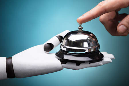 Person's Ringing Service Bell Hold By Robot On Turquoise Background Archivio Fotografico