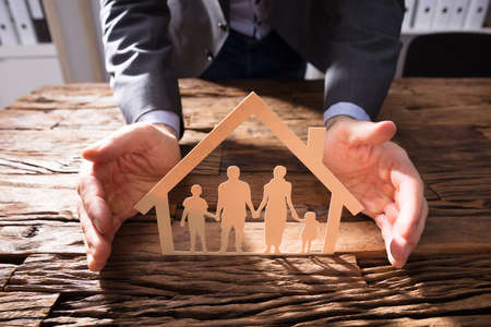 Businesspersons Hand Protecting House Model And Family Paper Cut Out On Wooden Desk Stock Photo