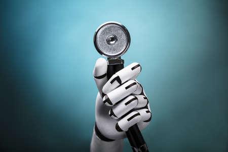 カラフルな背景に聴診器を持つロボットの手のクローズアップ 写真素材