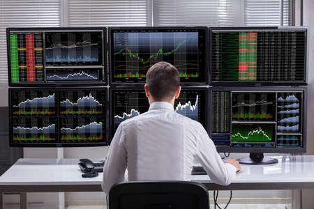 vista lateral de un joven hombre de valores de control de valores de gráfico en la pantalla de múltiples ordenadores