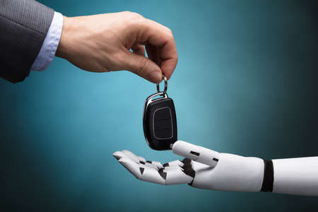 Close-up Of A Businesspersons Hand Giving Car Key To Robot On Grey Background