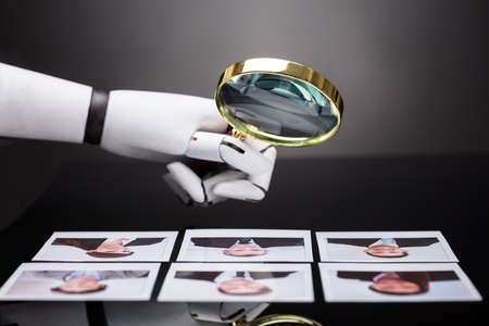 Close-up Of A Robots Hand Looking At Candidate Photograph With Magnifying Glass