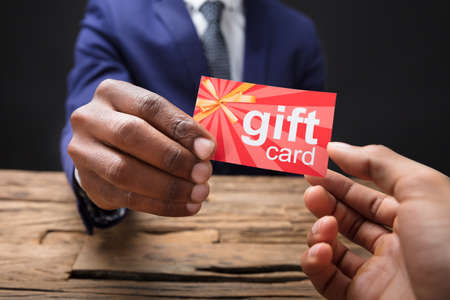 Close-up Of A Businessman's Hand Giving Gift Card To His Partner In Office