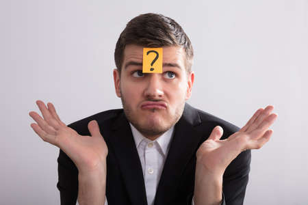 Close-up Of A Young Businessman With Sticky Notes On His Forehead Showing Question Mark Sign