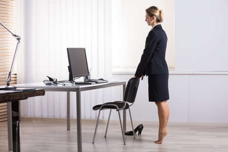 0f294e191ad2b3 Young Businesswoman Stretching Her Legs At Workplace