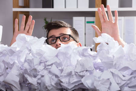 Close-up Of Businessman Wearing Spectacles Behind Heap Of Crumpled Paper In Office