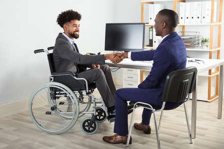 deux hommes d & # 39 ; affaires heureux assis sur fauteuil roulant et chaise se serrant la main devant l & # 39 ; ordinateur Banque d'images