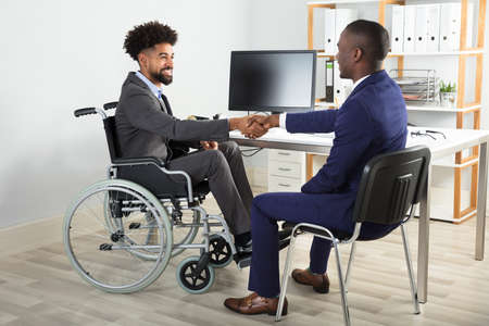 Two Happy Businessmen Sitting On Wheelchair And Chair Shaking Hands In Front Of Computer Reklamní fotografie