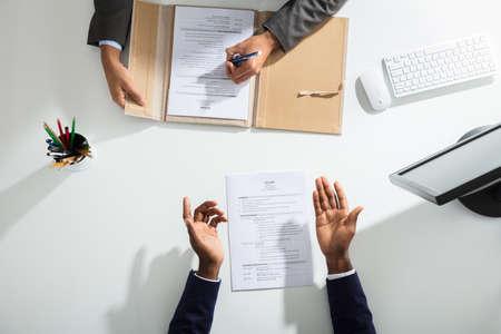 Podwyższone Widok Biznesmena I Kandydatów Strony Z CV Na Białym Biurku Zdjęcie Seryjne