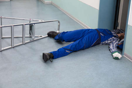Unconscious Handyman Fallen From Ladder With Equipments Lying On Floor Stock Photo