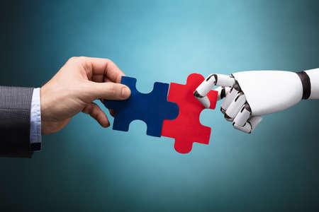 Unternehmer und Roboter , die Puzzlespiel auf Türkishintergrund halten
