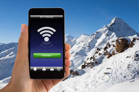 Close-up Of Hand Holding Mobile Phone With Wireless internet Signal In Snowy Mountain