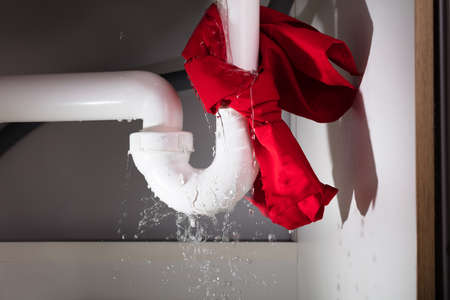 Close-up Of Red Napkin Tied Under The Leakage White Sink Pipe