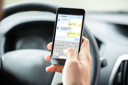 Close-up Of Person's Hand With Mobilephone Text Messaging Inside Car Foto de archivo