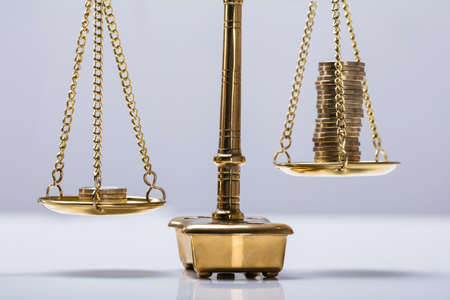 Close-up Of Coins Stack On The Golden Scale Against White Background