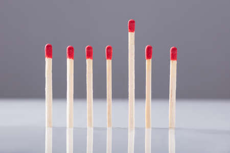 Raised Up Stick Among Unused Matchstick In A Row Against Grey Background Stock Photo