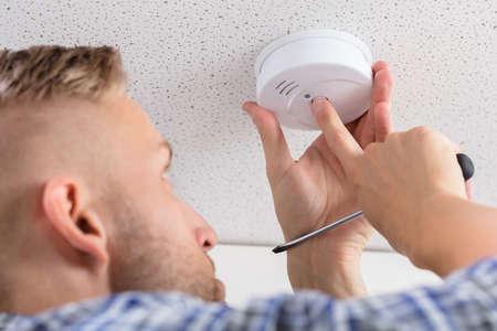 Lage hoekmening van de hand die van een persoon rookdetector thuis installeren op plafondmuur Stockfoto
