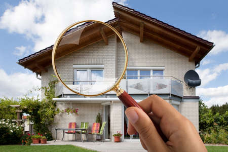 Close-up Of Person's Hand Holding Magnifying Glass Over Luxury House Outdoors Archivio Fotografico