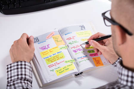 Close-up Of Man Writing Important Notes In Diary With Pen