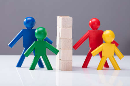 Close-up Of Multi Colored Human Figures Separated By Stacked Wooden Blocks Against Grey Background