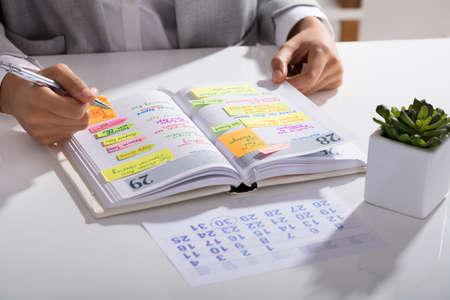 Gros plan d'une femme d'affaires établissant l'ordre du jour sur un organiseur personnel au lieu de travail