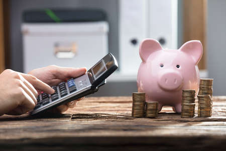 Businesspersons Hand Using Calculator With Stacked Coins And Piggy Bank On Wooden Desk Stock Photo