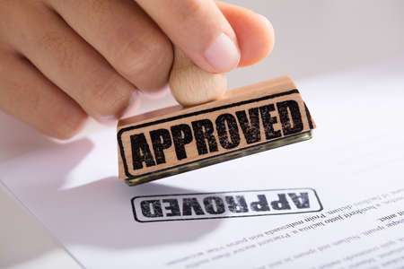 Close-up Of Person's Hand Approving Contract Form
