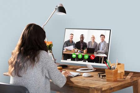 Vrouwen Videoconferentie met Glimlachende Mannelijke en Vrouwelijke Collega's op Computer Stockfoto