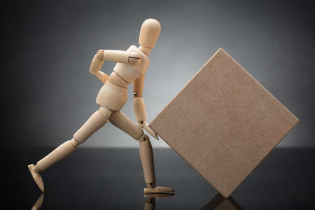 Side View Of A Wooden Dummy Lifting Cardboard Box Suffering From Back Pain
