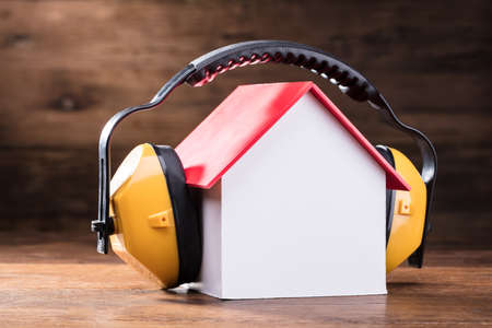 Close-up Of Working Yellow Protective Headphone On The House Model Over The Wooden Table