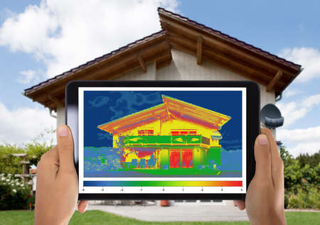 Close-up Of Person Detecting Heat Loss Outside The House Using Digital Tablet