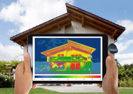 Gros plan d'une personne détectant une perte de chaleur à l'extérieur de la maison à l'aide d'une tablette numérique