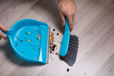 Close-up Of Male Sweeping Wooden Floor With Small Whisk Broom And Dustpan Stock Photo