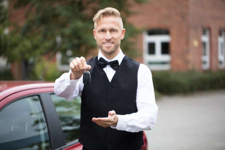Portrait Of A Handsome Male Valet Holding Car Keys Outdoors Stock Photo