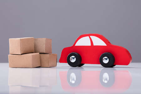 Red Car And Cardboard Boxes On White Desk Against Grey Background