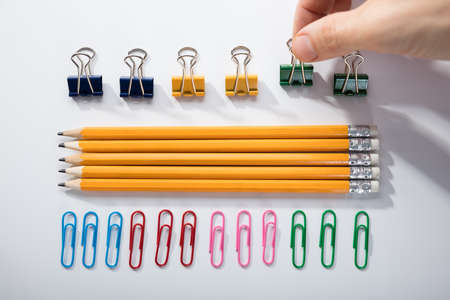 Person's Finger Arranging The Pencils With Row Of Pins Rubber And Pen On White Background