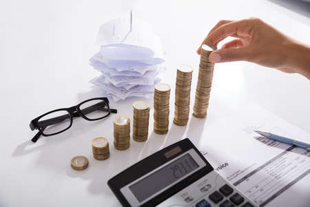 Moedas De Empilhamento Do Contador Na Mesa. Salvar o conceito do dinheiro
