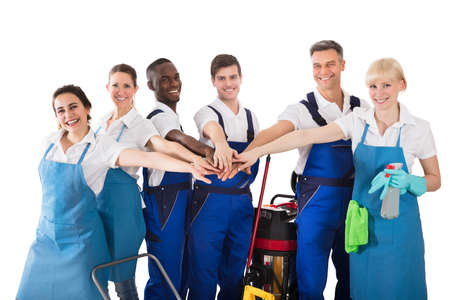 Group Of Happy Janitors Stacking Hands Isolated On White Background