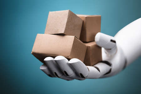Close-up Of A Robots Hand Holding Cardboard Boxes On Turquoise Background