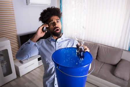 Worried Young Man Calling Plumber While Leakage Water Falling Into Bucket At Home
