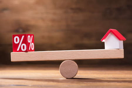Balancing Of Percentage Red Block And House Model On The Small Seesaw Stock Photo