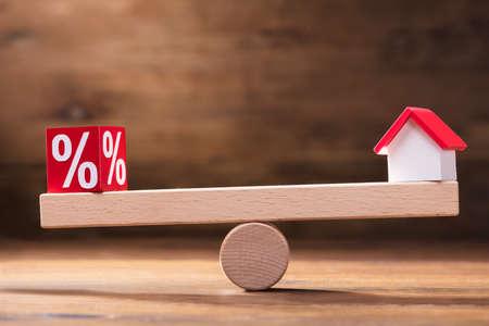 Równoważenie procentowego czerwonego bloku i modelu domu na małej huśtawce