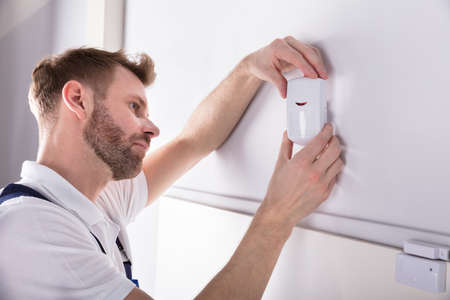Close-up Of Young Male Electrician Installing Security System Door Sensor On Wall Foto de archivo