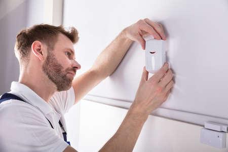 Zbliżenie młodego mężczyzny elektryka instalacji czujnika drzwi systemu bezpieczeństwa na ścianie