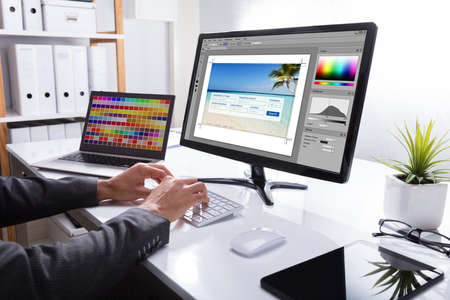 Close-up Of A Designers Hand Editing Photo On Computer In Office