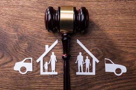 Sędzia młotek między rodziną wycinanki z papieru podzielonego i samochodem na drewnianym biurku